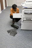 Office worker looking at photocopier Royalty Free Stock Photography