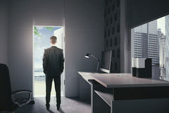 Office worker looking at seashore. Businessman standing in modern office interior with open door looking at seashore. Concept of choice between career Stock Photos