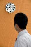 Office worker looking at a wall clock Royalty Free Stock Image