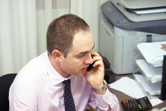 Office worker man answers the call. Businessman talking on phone at work royalty free stock photos