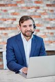 Office worker man,with headphones on head, sitting at desk with laptop and smiling. stock photography