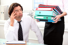 Office worker is overwhelmed. Office worker overwhelmed by load of work Royalty Free Stock Image