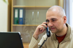 Office worker on the phone. Office worker with laptop speaking on the phone Stock Images