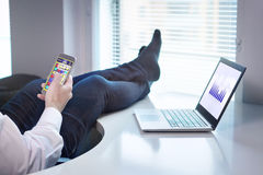 Office worker playing mobile game. Lazy office worker playing mobile game with smartphone during work hours. Avoiding his job and being lazy with feet and socks Royalty Free Stock Photos
