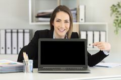 Office worker pointing at a laptop screen mockup. Front view portrait of a happy office worker pointing at a laptop screen mockup Royalty Free Stock Photography