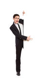 Office worker pointing at white banner. Shouting young man in black suit pointing at the banner. Full length studio shot isolated on white Stock Photography