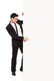 Office worker pointing at white banner. Young man in black suit pointing at the banner. Full length studio shot isolated on white Royalty Free Stock Photography