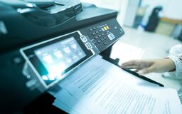 Free Office Worker Print Paper On Multifunction Laser Printer. Copy, Print, Scan, And Fax Machine In Office. Modern Print Technology. Stock Image - 216759901