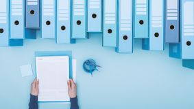 Office worker and archive binders. Office worker reading paperwork and archive binders, files database and management concept, top view royalty free stock photos