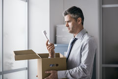 Office worker receiving a surprise call in a box. Shocked office worker receiving a surprise call inside a cardboard box, stressful job and stalking concept Stock Photos