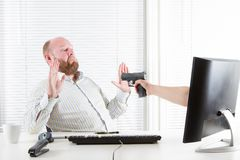 Businessman Threatened by Computer. Office worker robbed and threatened by the computer. Internet fraud royalty free stock photo