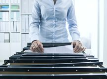 Office worker searching files in the archive. Female office worker searching files and paperwork in the archive, she is checking folders in a filing cabinet royalty free stock image