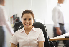 Office worker seating and smiling, portrait at the office Stock Images