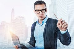 Serious intelligent man holding a laptop royalty free stock image