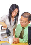 Office worker serving coffee to a man stock photography