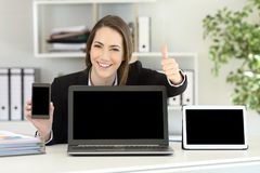 Office worker showing multiple device screens. A laptop tablet and phone mockups royalty free stock photo