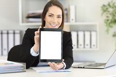 Office worker showing a tablet screen mockup. Happy office worker showing to camera a tablet screen mockup Royalty Free Stock Photo