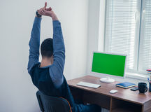 Office worker sitting at computer with Chromakey on monitor. Tiredman office worker sitting at computer with Chromakey and stretching himself. Office concept Stock Images