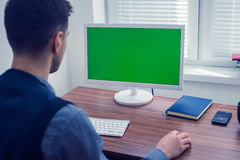 Office worker sitting at computer with Chromakey on monitor. Young man office worker sitting at his desk working at computer with Chromakey on monitor. Office Stock Photography