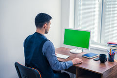 Office worker sitting at computer with Chromakey on monitor. Young man office worker sitting at computer with Chromakey and looking on monitor. Office concept Stock Photography