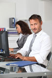 Office worker sitting in front of computer Royalty Free Stock Images
