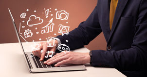 Office worker sitting in front of laptop. An elegant businessman sitting at desk and pushing the buttons of his laptop keyboard while working on everyday office Stock Photos