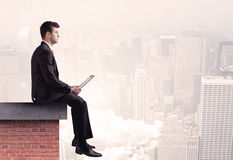 Office worker sitting on rooftop in city Royalty Free Stock Photo