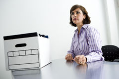 Office worker sitting at table with box of files Stock Images