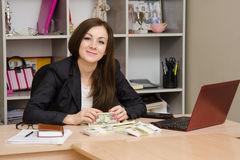 Office worker sitting at table with a bunch of money and looks in picture Stock Photography