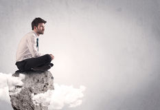 Office worker sitting on top of a rock Royalty Free Stock Image