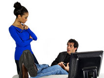 Office worker slacking. Manager is upset at male office worker, catches him slacking at work and texting on his cell phone royalty free stock images