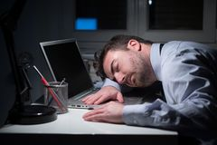 Tired businessman falling asleep on the desk Royalty Free Stock Photos