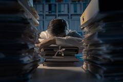 Office worker sleeping on the desk. Late at night, he is exhausted and overloaded with work, his desktop is covered with paperwork: deadlines and overtime work royalty free stock photos