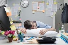 Office worker sleeping on desk stock photography