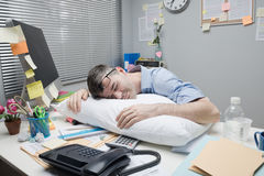 Office worker sleeping on desk Royalty Free Stock Photos