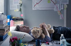 Office worker sleeping at work with teddy bear Royalty Free Stock Photo