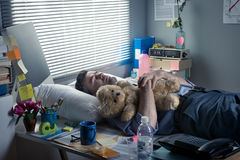 Office worker sleeping at work with teddy bear Royalty Free Stock Photos
