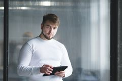 Office worker standing with a tablet in his hands against the background of the wall and looking at the camera. A man is an office worker standing with a tablet Stock Image