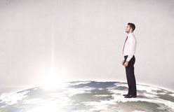 Office worker standing on top of a drawn world globe while celebrating his successful career concept. A young elegant office worker standing on top of a drawn Stock Image