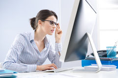 Office worker staring at computer screen. Young office worker staring at computer screen and adjusting glasses Stock Photos