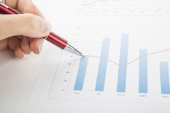 Office worker studying the chart with a pen Stock Photo