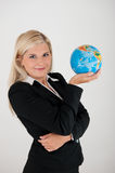 Office worker in a suit holding a globe. Picture of a young friendly beautiful female office worker in a suit holding a globe royalty free stock photos