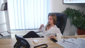 Office worker taking a coffee break with her bare feet raised up on the desk and a cup of espresso in her hands stock footage