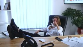 Office worker taking a coffee break with her bare feet raised up on the desk and a cup of espresso in her hands stock video footage
