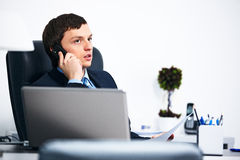 Office worker talking on cell phone in office Royalty Free Stock Images