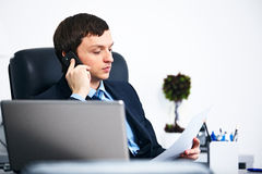 Office worker talking on cell phone in office Stock Images