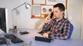 Office worker talking on a mobile phone with his client sitting in his office. Young office worker in casual clothes talking on a mobile phone with his client stock video footage