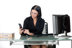 Office worker texting on cellphone. Woman seated at a glass desk, texting with a cellular phone Stock Photography