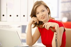 Office worker thinking with phone in hand Stock Images