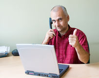 Office worker with thumb up. Happy office worker on the phone working at the desk with laptop royalty free stock image